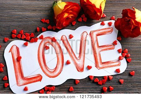 Valentine's Day concept. Painted word LOVE and roses on wooden background, close up