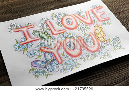 Bright picture with phrase I LOVE YOU on wooden table, close up
