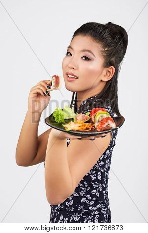 Portrait of the Happy Young Japanese Woman Eating Sushi