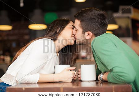 Kissing Across The Table In A Restaurant