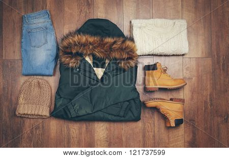 Set of beautiful winter female clothes on wooden background