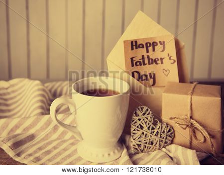 Greeting card for Happy Father's Day with tea cup, gift box on wooden table