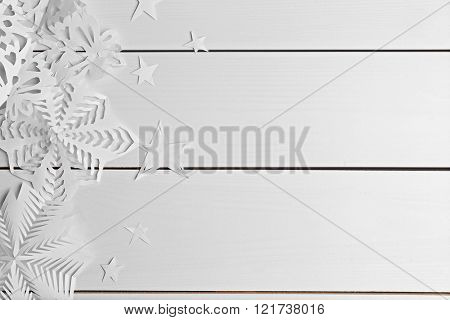 Winter background with hand-made paper snowflakes on wooden background