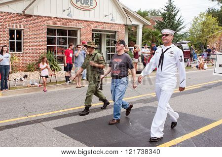 ALPHARETTA, GA - AUGUST 2015: Three combat veterans representing the Army Navy and Marines walk in the annual Old Soldiers Day Parade in Alpharetta GA on August 1 2015.