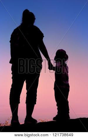 Silhouette Of Mother And Child Hikers Enjoying The View At The Top Of A Mountain.