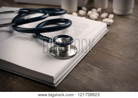 Stethoscope with pills and book, closeup