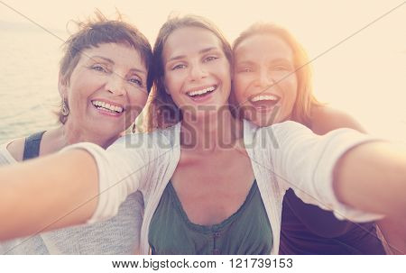 mother and two adult daughters are doing Selfe on the beach
