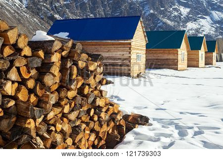 Pile Of Firewood Stacked Up In Front Of A Houses. Rural Scene.