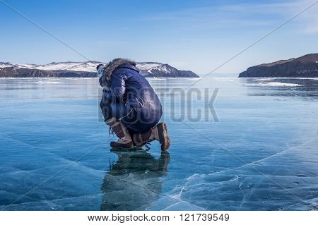 Woman sitting on the frozen Lake Baikal