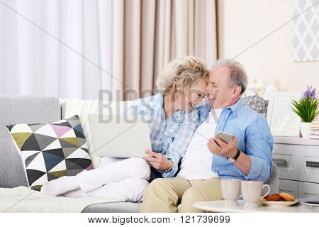 Mature couple sitting together with laptop and mobile phone at home