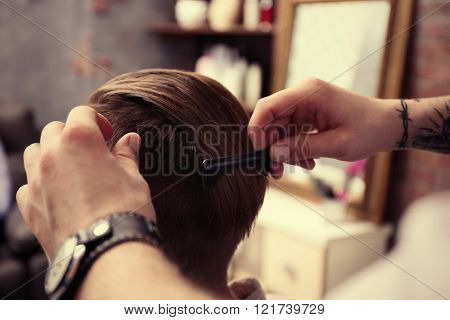 Professional barber making stylish man haircut