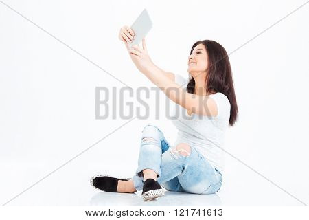 Smiling casual woman making selfie photo on tablet computer isolated on a white background