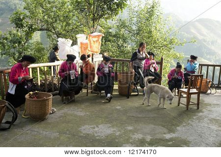 GUILIN, CHINA - MAY 23: Farm womenfolk work on clothes embroidery in front of their home in Longji on May 23, 2010. The traditional costumes and lifestyle make Lingji a popular tourist destination.