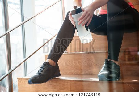 Beautiful slim legs of attractive woman athlete sitting on stairs in gym with bottle of water