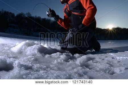 Man ice fishing in the cold winter on a lake