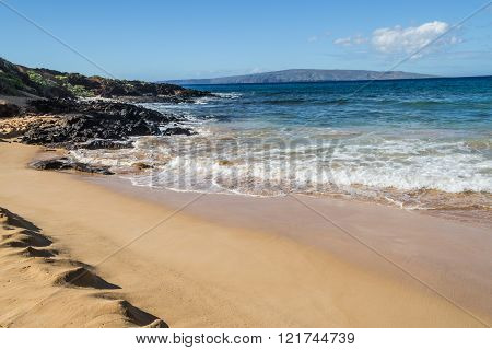 Wailea Beach Maui tawny-colored sand is lined by palm trees and a paved walkway connecting the shoreline to the area's hotels shops and restaurants. ** Note: Soft Focus at 100%, best at smaller sizes