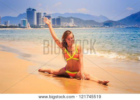 Blonde Slim Girl In Bikini Makes Split On Wet Sand Smiles At Sea