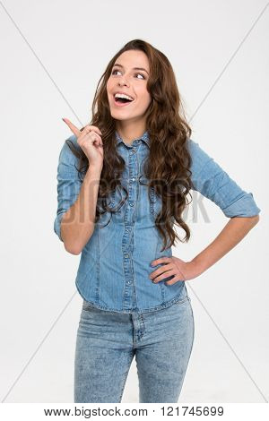 Cheerful excited young woman in jeans shirt standing and pointing away over white background