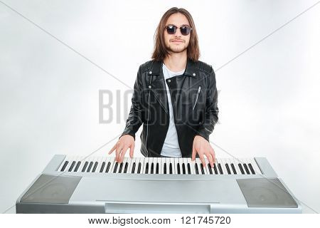 Smiling attractive young man with long hair in sunglasses playing on synthesizer over white background