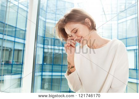 Cute lovely smiling young woman standing near the window in office and laughing