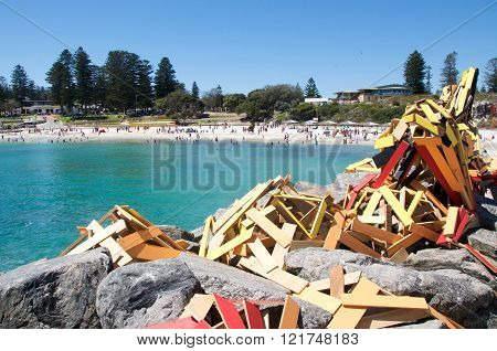 COTTESLOE,WA,AUSTRALIA-MARCH 12,2016: Colourful wooden sculpture on rocky breakwater with tourists on the beach at the