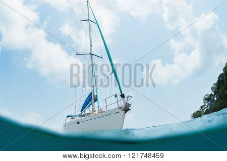 White sail boat in the sea. Underwater splited shoot