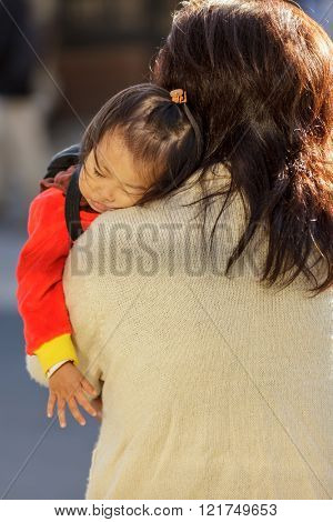 KYOTO, JAPAN, NOVEMBER 20, 2011 : A mother is carrying her sleeping little daughter on her shoulder in a street of Kyoto, Japan