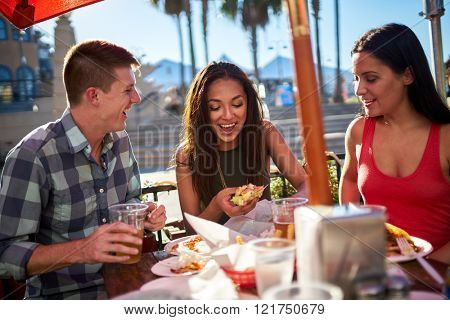 friends having fun at outdoor restaurant eating and drinking
