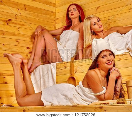 Happy girlfriends relaxing in sauna. Women talking about sauna healthy.