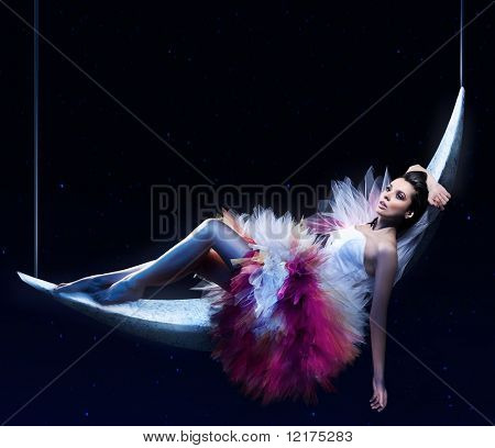 Beauty brunette lying on the crescent moon