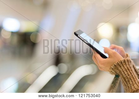 Woman use of mobile phone at shopping center