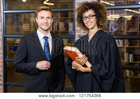 Portrait of businessman standing with lawyer near library in office