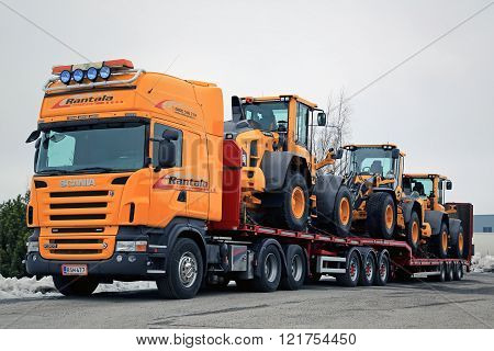 LIETO, FINLAND - MARCH 12, 2016: Scania R500 V8 truck is ready to haul three Volvo L60H wheel loaders. The operating weight of Volvo L60H is 11.0-13.6 tonnes.