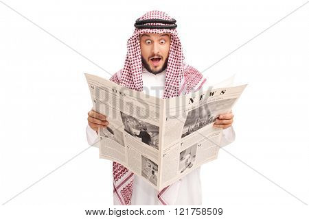 Surprised young Arab reading a newspaper and making a baffled expression isolated on white background