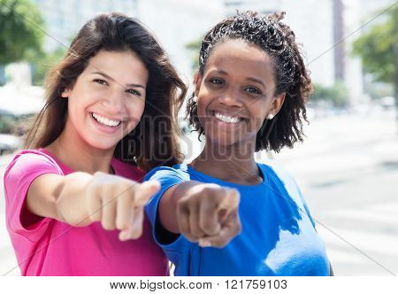 Two African And Caucasian Women Pointing At Camera In The City