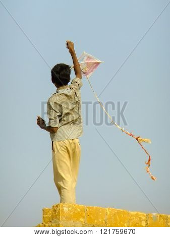Jaisalmer, India - February 18: Unidentified Boy Flies Kite From The Roof Of Traditional House On Fe