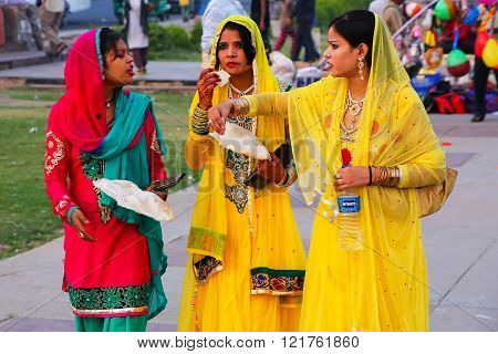 JAIPUR, INDIA - NOVEMBER 13: Unidentified women walk and eat by Man Sagar Lake on November 13, 2014 in Jaipur, India. Jaipur is the capital and largest city of Rajasthan.