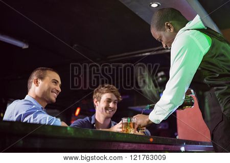 Bartender serving whiskey to two men at bar counter in bar