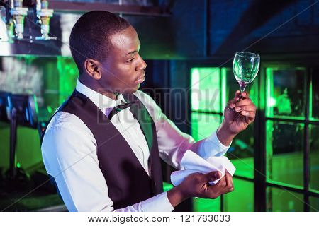 Barkeeper standing at bar counter and checking a wine glass after cleaning