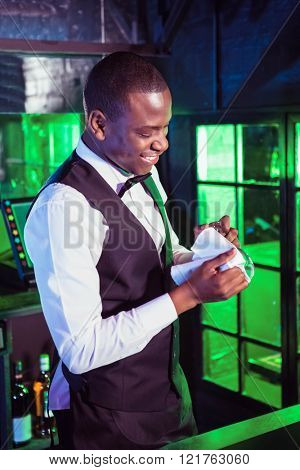 Smiling bartender cleaning a glass at bar counter in bar