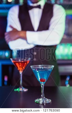 Blue and orange glasses of cocktail on bar counter and bartender standing in background