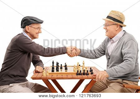 Two senior gentlemen shaking hands after playing a game of chess isolated on white background