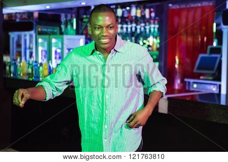 Happy man dancing in front of bar counter in bar