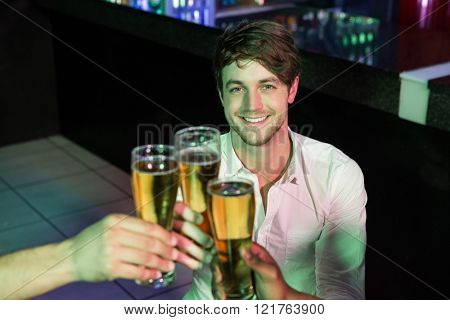 Happy man toasting his glass of beer with friends in bar