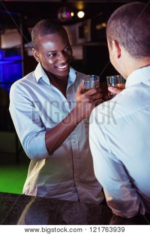 Two men toasting with glass of whiskey at bar counter in bar