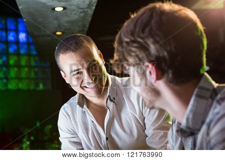 Happy men smiling and talking near a bar counter in bar