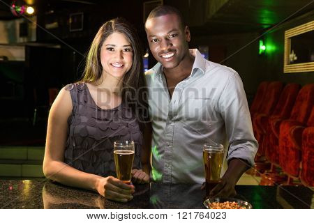 Portrait of couple having beer at bar counter in bar
