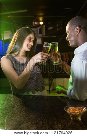 Couple toasting their beer glasses at bar counter in bar