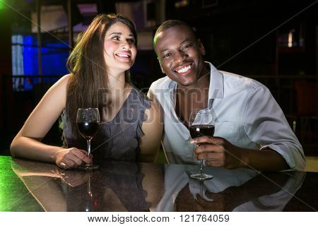 Couple smiling while having red wine at bar counter in bar