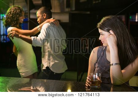 Unhappy woman looking at a couple dancing behind her in bar